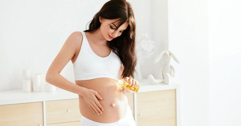 Kobieta w ciąży smaruje się samoopalaczem