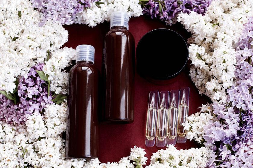 Ampułki do włosów na tle kwiatów