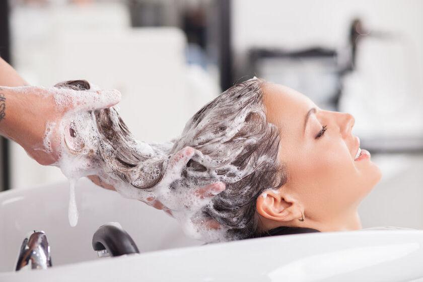 Fryzjer myje klientce włosy