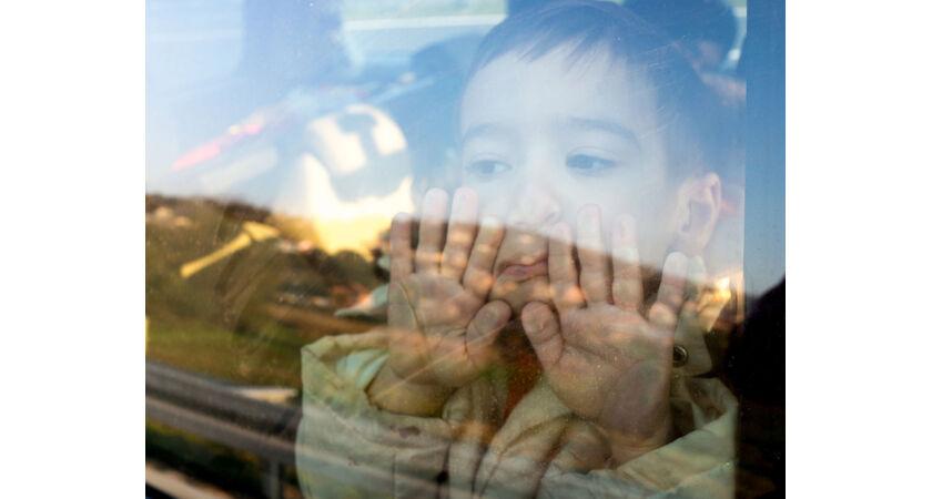 Chłopiec przykładający twarz do szyby samochodu