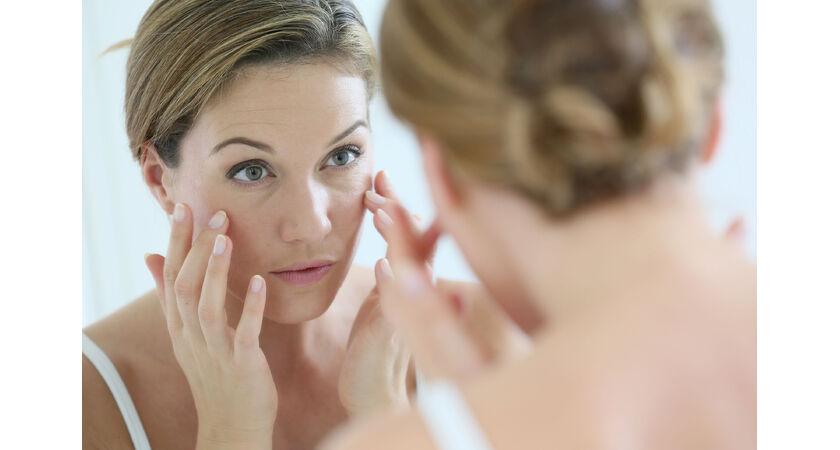 Dojrzała kobieta oglądająca w lustrze zmarszczki