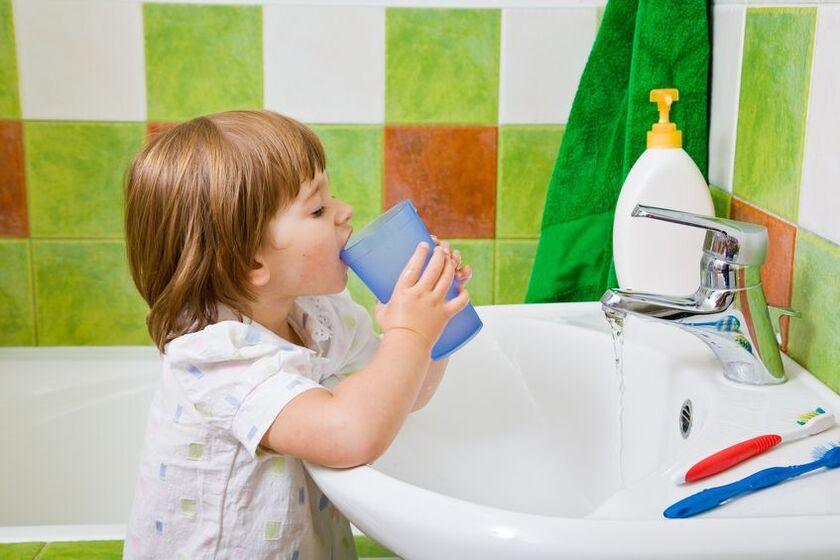 Dziecko płucze jamę ustną po myciu zębów