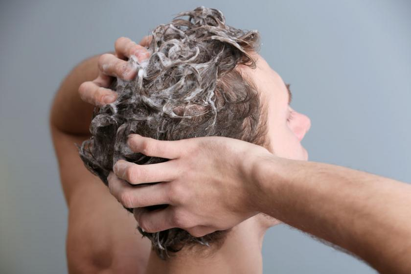 Mężczyzna myje włosy szamponem
