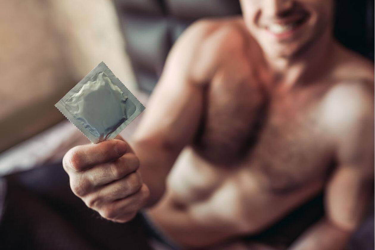 Mężczyzna trzyma w dłoni prezerwatywę
