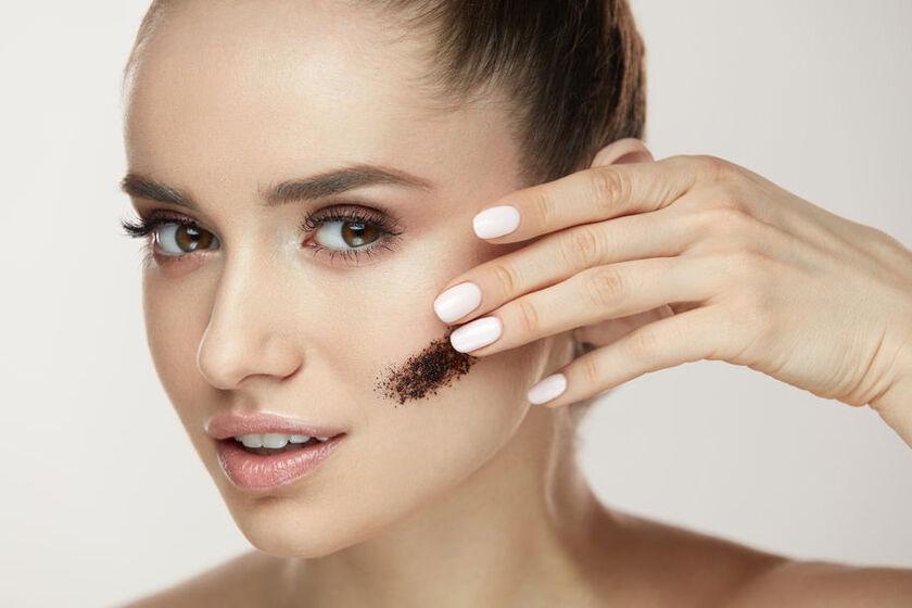 Piękna kobieta robi peeling kawowy twarzy