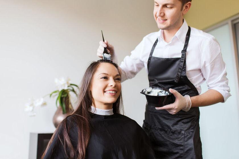 Fryzjer nakłada klientce farbę na włosy