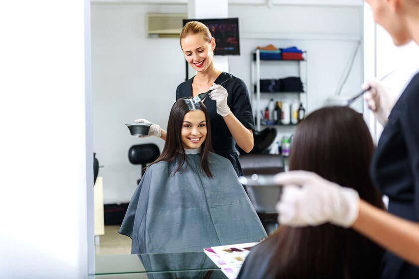Fryzjerka nakłada klientce farbę na włosy