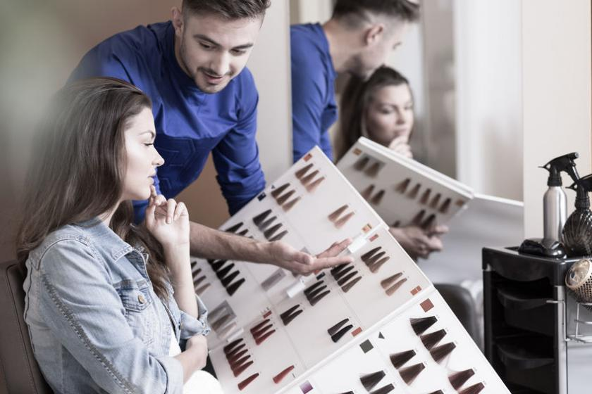 Fryzjer pokazuje klientce paletę kolorów farb do włosów