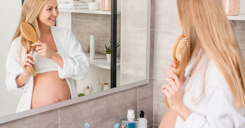 Kobieta w ciąży czesze włosy przed lustrem
