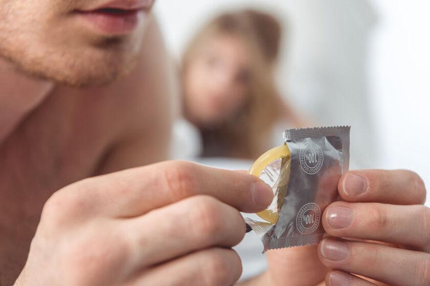 Mężczyzna trzyma w dłoniach prezerwatywę