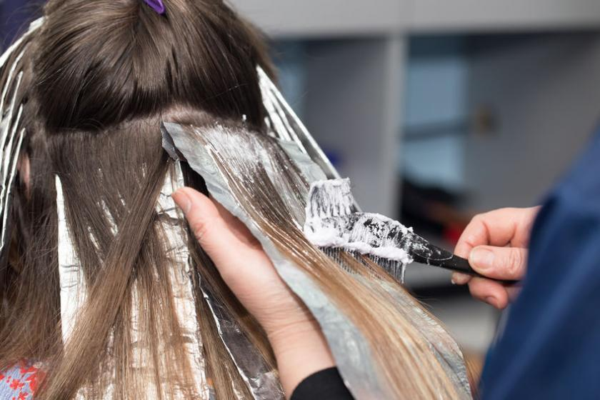 Fryzjer robi pasemka na jasnych włosach