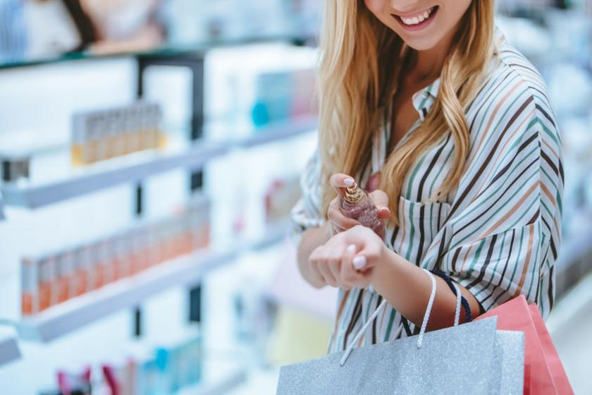 Kobieta testuje wodę toaletową w perfumerii