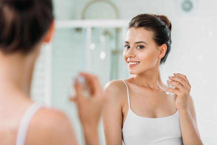 Kobieta spryskuje szyję perfumami