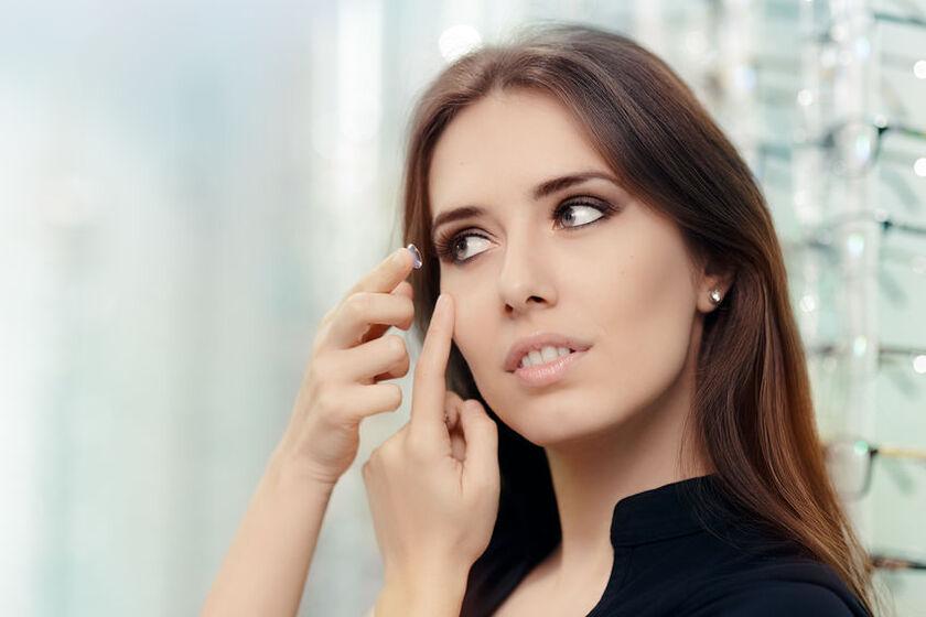 Kobieta wkłada soczewki toryczne