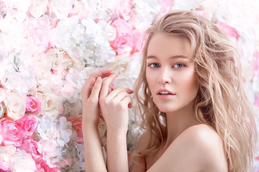 Piękna kobieta z burzą włosów na tle kwiatów