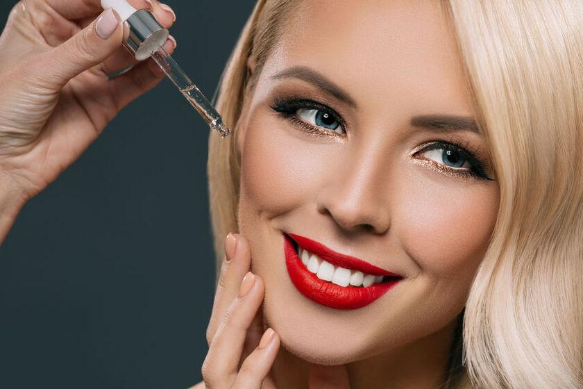 Piękna kobieta aplikuje na twarz serum nawilżające