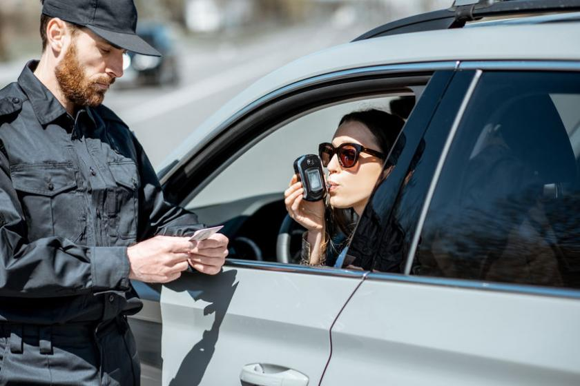Policjant bada trzeźwość kierującej alkomatem