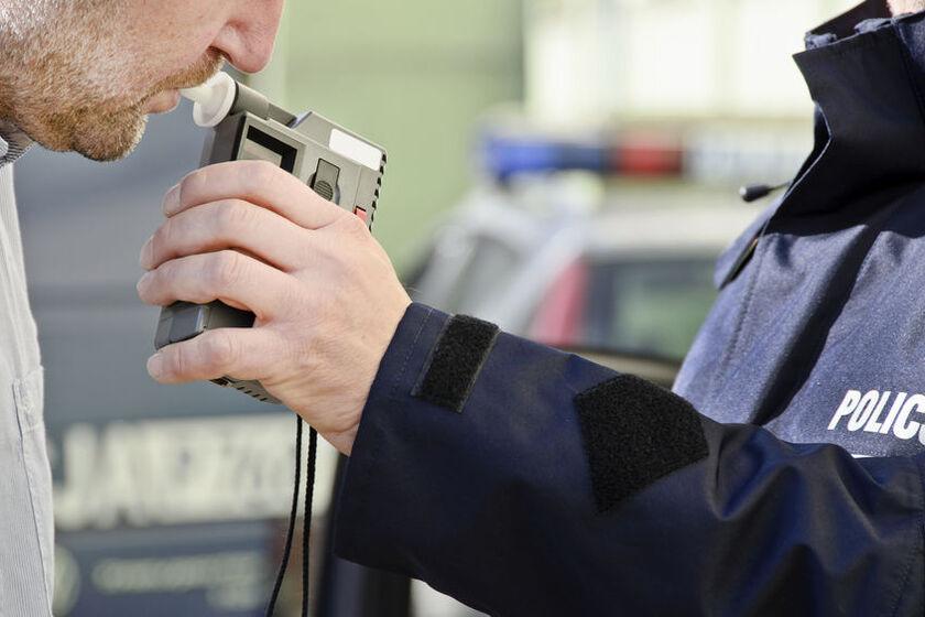Policjant bada trzeźwość kierowcy alkomatem z atestem