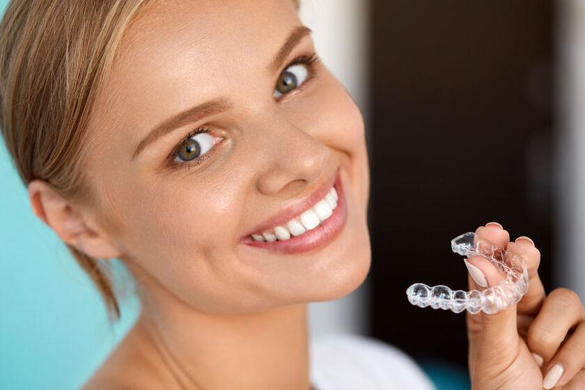 Kobieta trzyma w dłoni nakładki do wybielania zębów