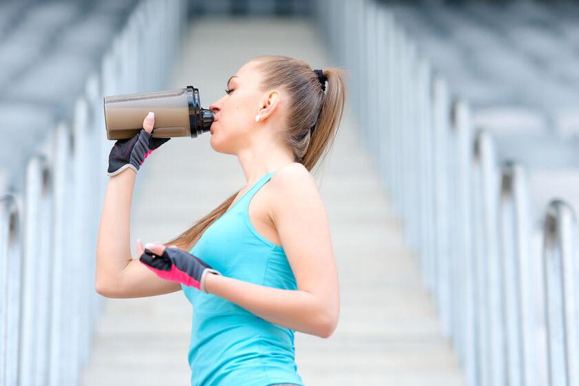Kobieta pije odżywkę białkową