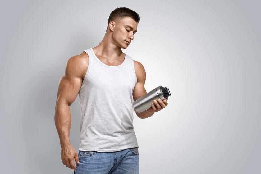 Mężczyzna trzyma w dłoni odżywkę białkową