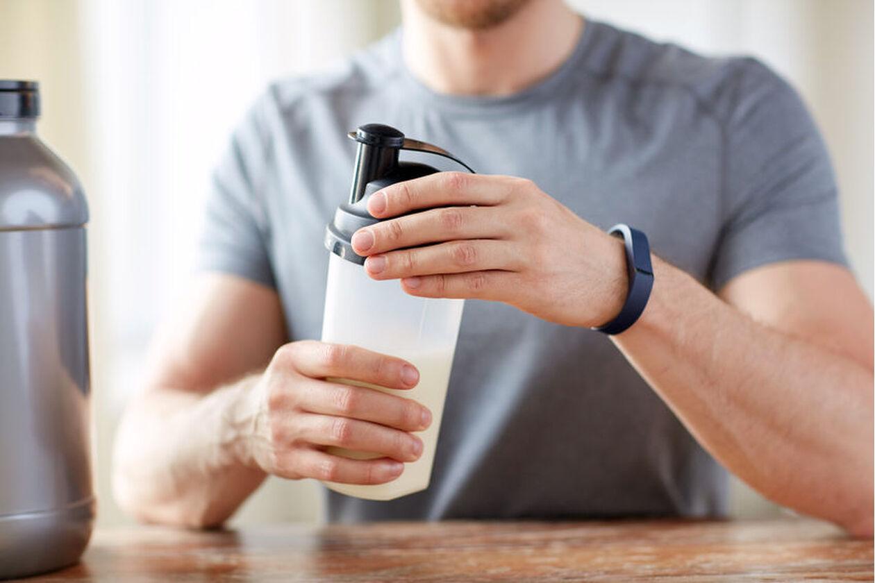 Dobrze zbudowany mężczyzna przygotowuje odżywkęna bazie kazeiny micelarnej