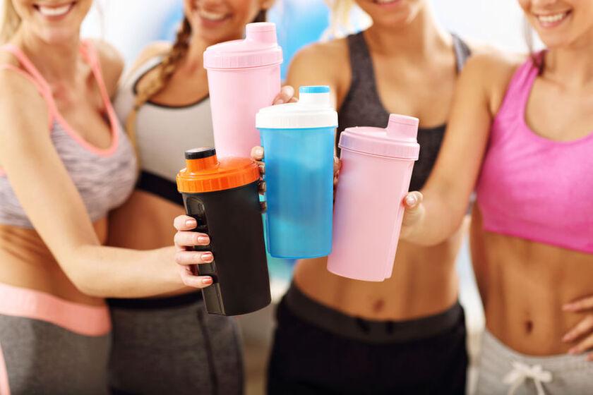 Dziewczyny stukająsięshakerami do odżywek białkowych po treningu