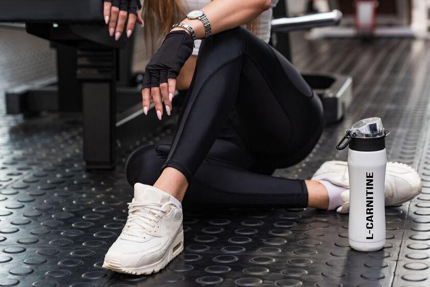 Kobieta na siłowni z shakerem zawierającym L-karnitynę