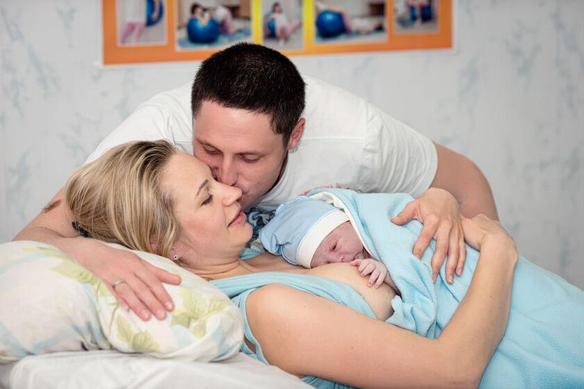 Kobieta z dzieckiem przy piersi po zabiegu cesarskiego cięcia