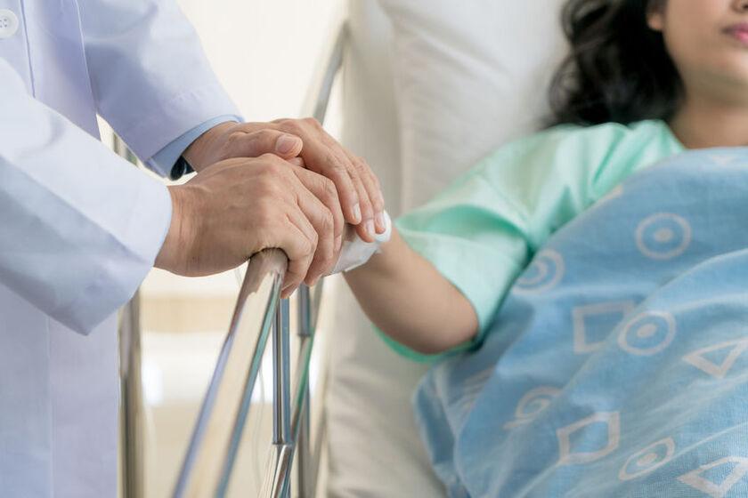 Lekarz trzyma za rękę kobietępo poronieniu