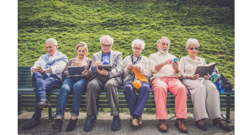 Grupa seniorów siedzi na ławce