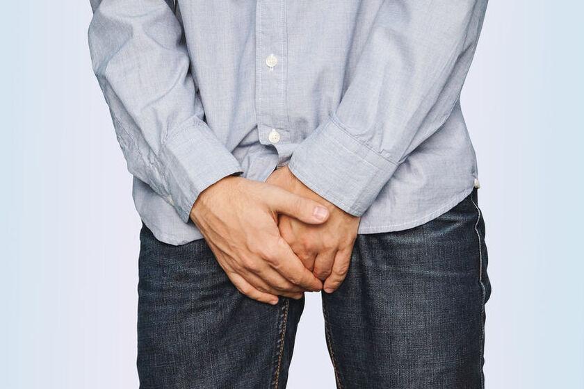 Mężczyzna trzymające dłonie na kroczu