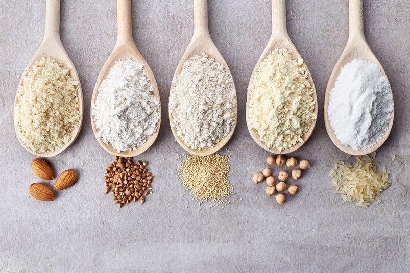 Różne rodzaje mąki bezglutenowej na drewnianych łyżkach