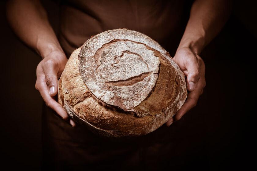Kobieta trzyma w dłoniach chleb
