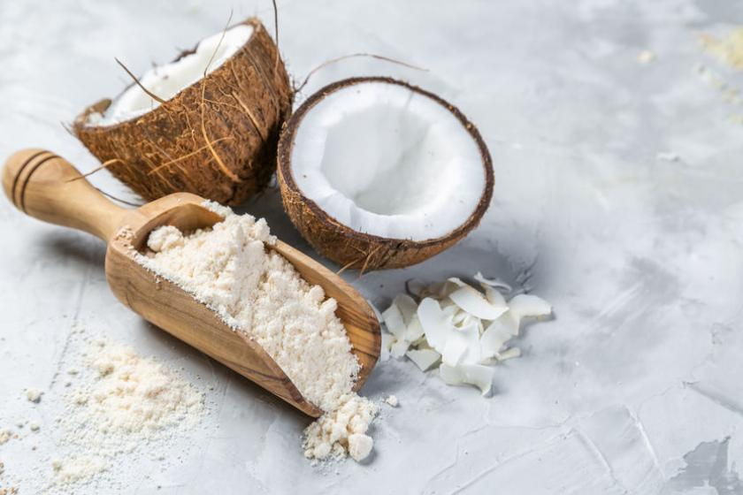 Mąka kokosowa na drewnianej łyżce i przepołowiony kokos