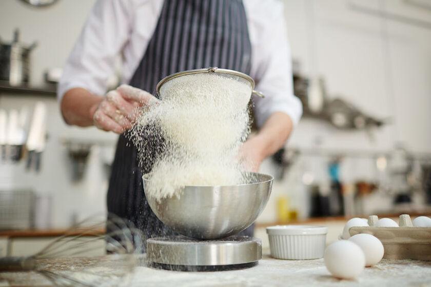 Kucharz przesiewa mąkę z samopszy