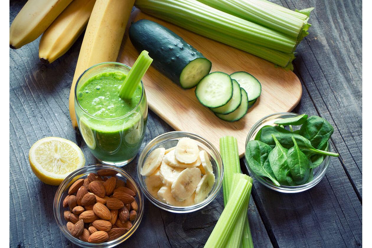 Szklanka soku z selera naciowego i różne warzywa w kuchni