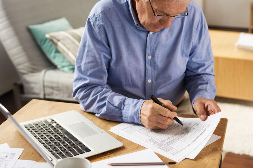 Starszy mężczyzna wypełnia wniosek o emeryturę