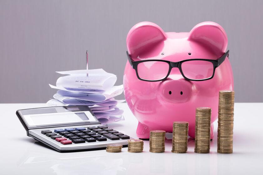 Świnka skarbonka, stos monet i kalkulator