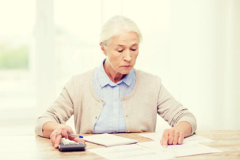 Starsza kobieta wylicza podatek