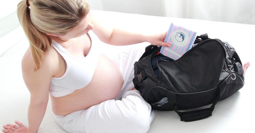 Ciężarna kobieta składająca ubranka dla dziecka