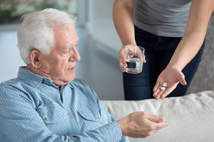 Starszy mężczyzna zażywa leki