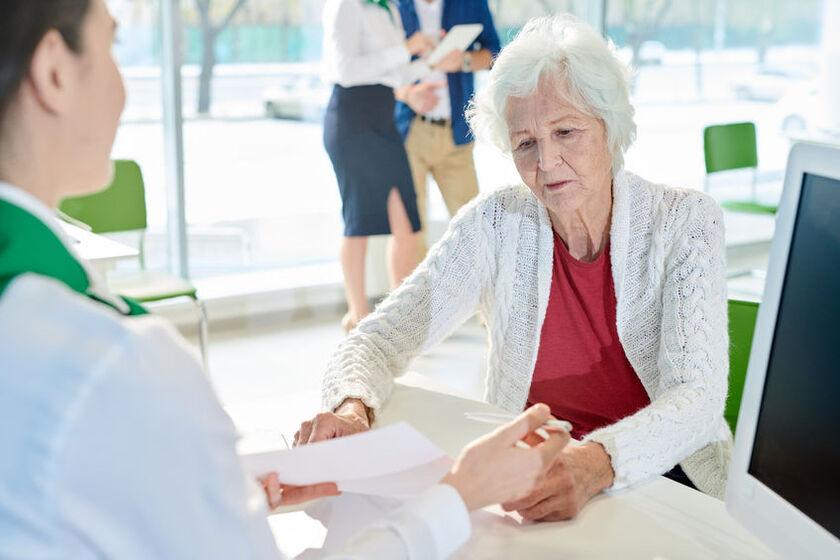 Starsza kobieta bierze pożyczkę gotówkową