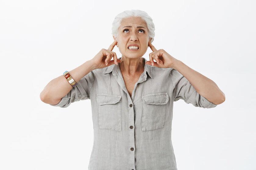 Starsza kobieta zatykająca uszy przez hałasującego sąsiada