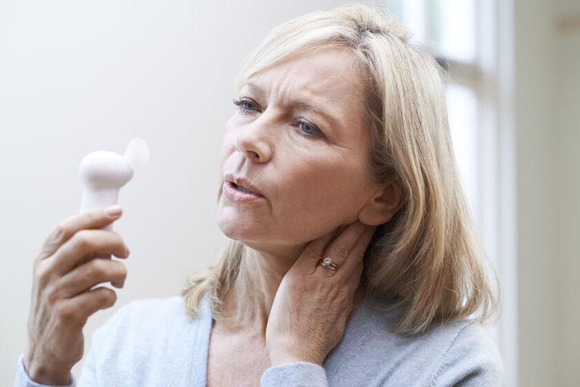 Kobieta w trakcie menopauzy odczuwa uderzenia gorąca