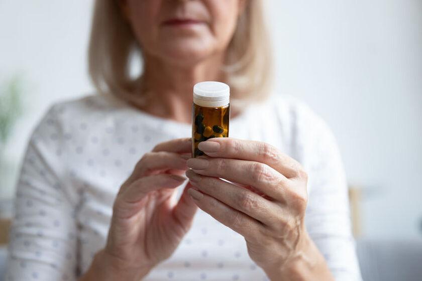 Kobieta łyka zioła na menopauzę