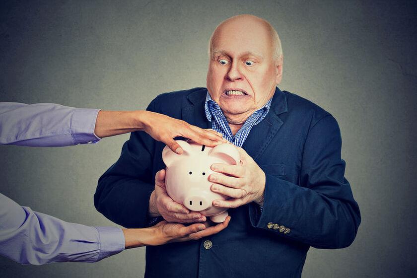 Starszy mężczyzna trzyma kurczowo świnkę skarbonkę