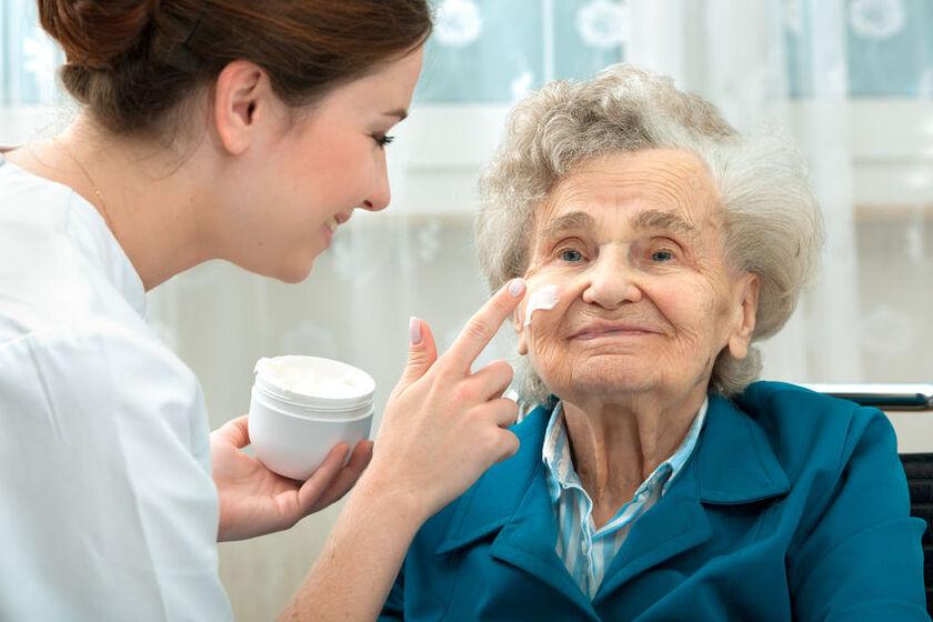 Lekarz smaruje twarz starszej kobiety kremem