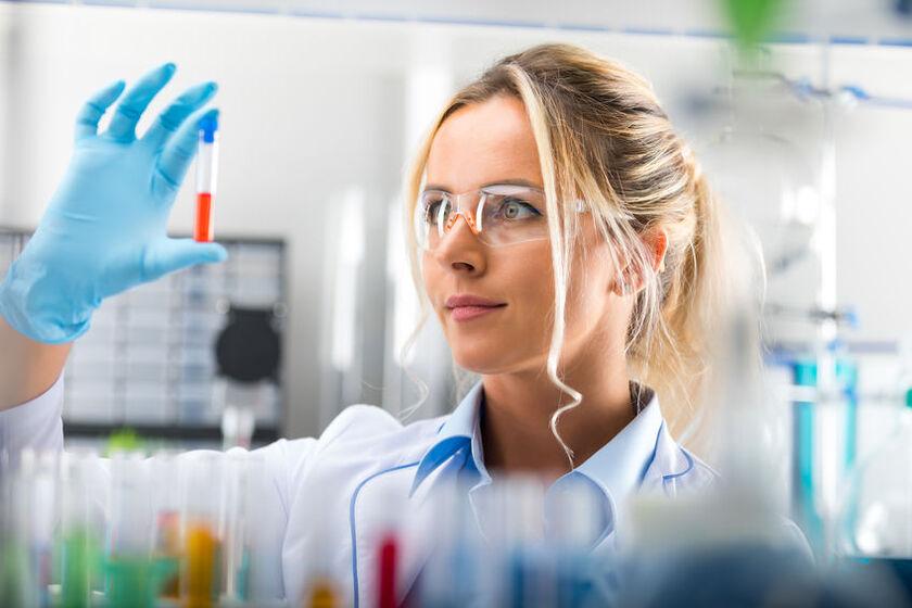 Kobieta trzyma w dłoni próbówkę do badania