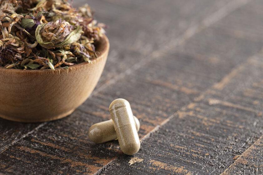 Ziołowe tabletki na menopauzę i miseczka z ziołami